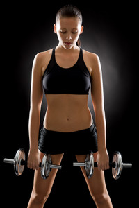 Fitness young woman holding adjustable dumbbells on black background