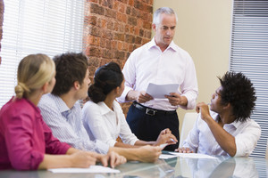 Five businesspeople in boardroom meeting