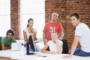 Five businesspeople in office space smiling