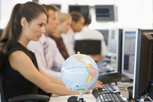 Five businesspeople in office space with desk globe in foreground