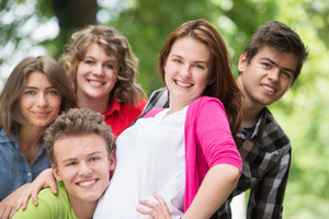 Five cheerful teenagers posing in woods