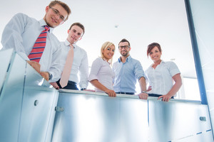 Five happy executive people behind a glass railing