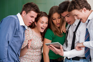 Five surprised students looking at a tablet screen