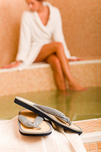 Flip-flops close-up relax spa pool woman wear bathrobe