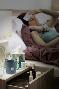Flu medicines on bedside table beside ill woman in bed