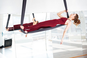 Focused beautiful young woman doing antigravity yoga in studio