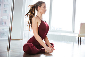 Focused pretty ypung woman with dreadlocks doing yoga in studio