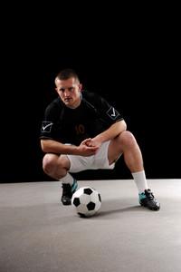 Footballer on black background