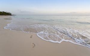 Footprints along the beach at sunset
