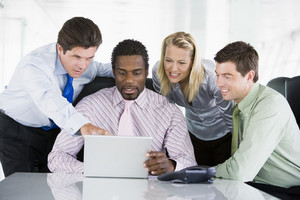 Four businesspeople in a boardroom pointing at laptop and smiling