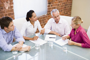 Four businesspeople in boardroom talking