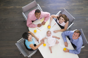 Four businesspeople in boardroom with a baby lying on the table