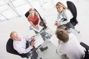 Four businesspeople in boardroom with paperwork smiling