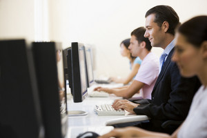 Four people sitting in computer room typing with one man in a suit