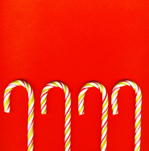 Four Red And Green Christmas Candy Canes Isolated On Red