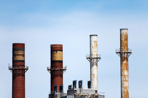 Four smoke stacks atop factories or industrial buildings in the skyline.