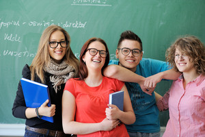 Four young people with glasses in front of chalkboard