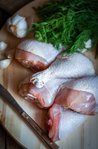 Fresh Raw Chicken Legs  On Kitchen Cutting Board With Dill And Garlic
