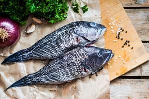 Fresh Sea Bass On Board Before Preparation On Rustic Wooden Background