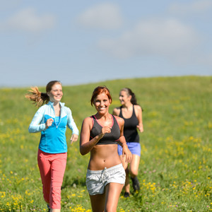 Friends enjoy running through sunny meadow smiling