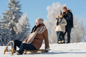 Friends enjoy sunny winter day on wooden sledge