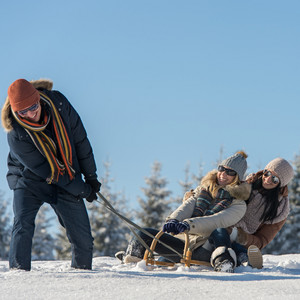 Friends having fun on snow sledge sunny wintertime
