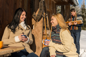 Friends spend holiday winter snow cottage enjoy tea outside