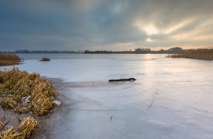 Frozen lake at sunrise landscape. Beautiful landscape of winter lake in Mazury lake district.