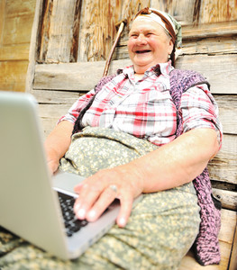 Full length of a senior woman sitting and using a laptop against