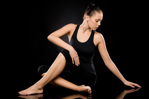 Full length of an attractive woman in spine twisting pose