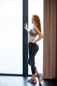 Full length portrait of a beautiful fitness woman looking at camera