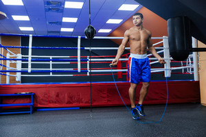 Full length portrait of a boxer jumping with skipping rope