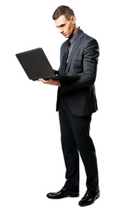 Full-length portrait of a businessman standing and using laptop isolated on a white background