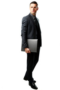 Full-length portrait of a businessman standing with laptop isolated on a white background