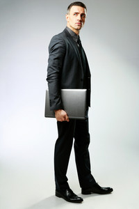 Full-length portrait of a businessman standing with laptop over gray background