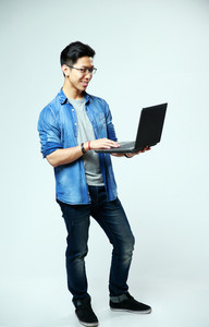 Full length portrait of a cheerful asian man using laptop on gray background