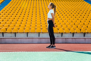 Full length portrait of a fitness woman resting on the stadium