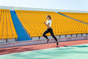 Full length portrait of a fitness woman running at stadium
