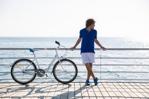Full length portrait of a handsome man with bicycle resting outdoors near the sea