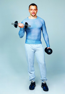 Full length portrait of a handsome sports man lifting dumbbell on gray background
