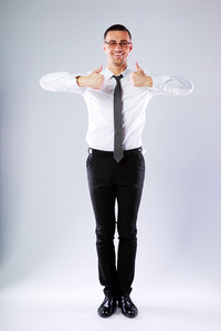 Full-length portrait of a happy businessman standing with thumbs up on gray background