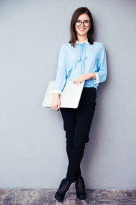 Full length portrait of a happy businesswoman holding laptop. Wearing in blue shirt and glasses. Looking at camera