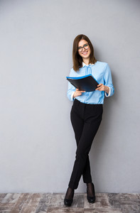 Full length portrait of a happy businesswoman standing with folder. Wearing in blue shirt