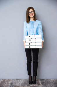 Full length portrait of a happy businesswoman standing with folders. Wearing in blue shirt and glasses. Looking at camera