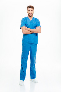 Full length portrait of a male doctor standing with arms folded isolated on a white background