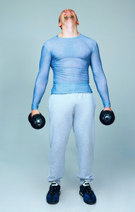 Full length portrait of a man standing with dumbbells and looking up on gray background