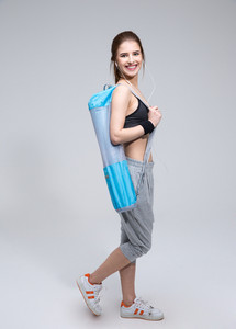Full length portrait of a smiling sporty woman with yoga mat