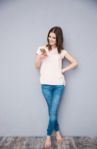 Full length portrait of a smiling woman using smartphone