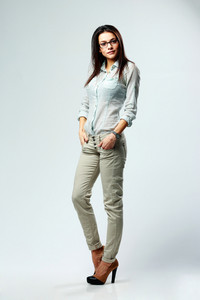 Full-length portrait of a young beautiful businesswoman standing on gray background