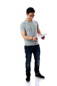 Full-length portrait of a young happy asian man standing with tablet computer over white background